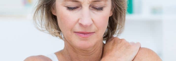 woman in pain, holding shoulder