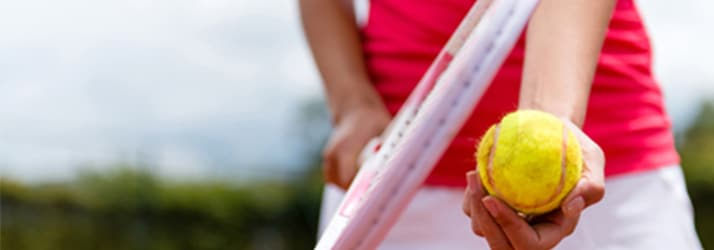woman holding tennis ball with racket in other hand